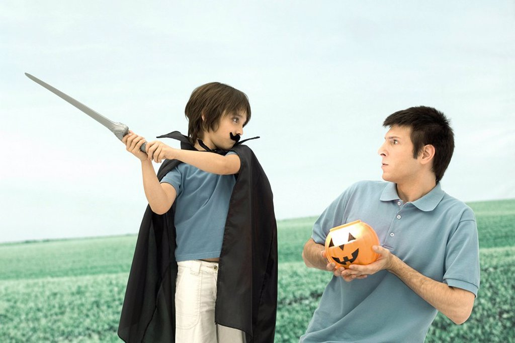 Father and son playing, man holding jack o´ lantern, boy swinging sword : Stock Photo