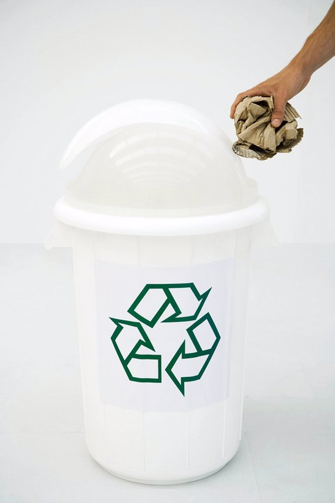 Man´s hand placing cardboard in recycling bin, cropped : Stock Photo