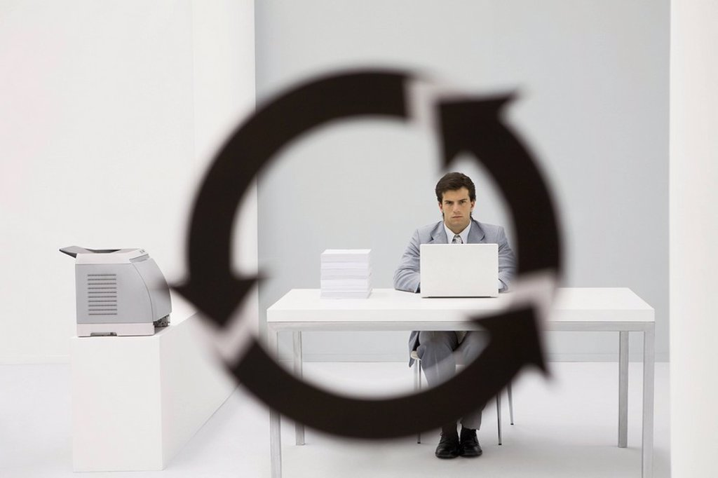 Professional man sitting in office, looking at camera through arrow symbol in foreground : Stock Photo