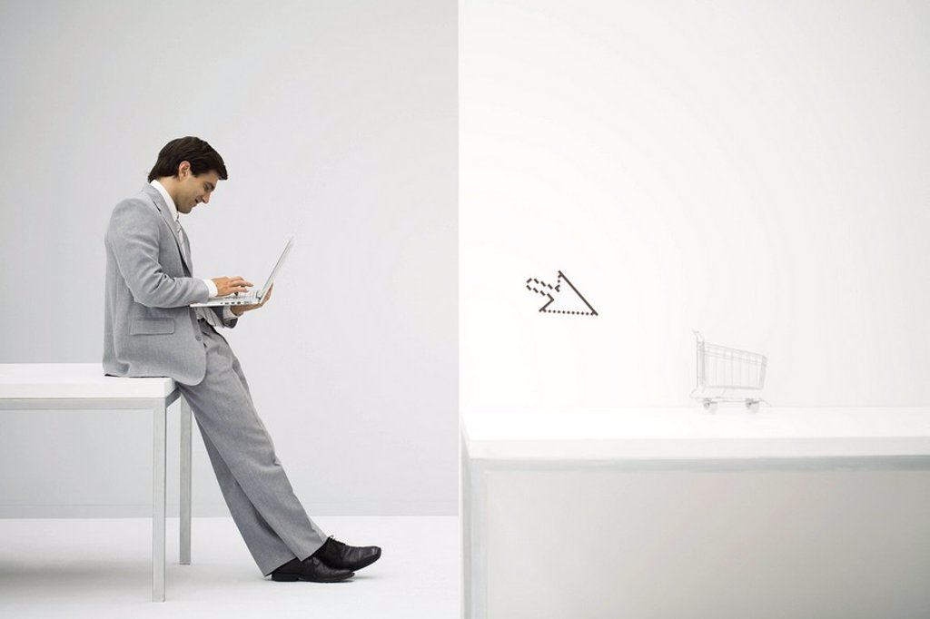 Businessman sitting on desk, shopping online, shopping cart and cursor in foreground : Stock Photo