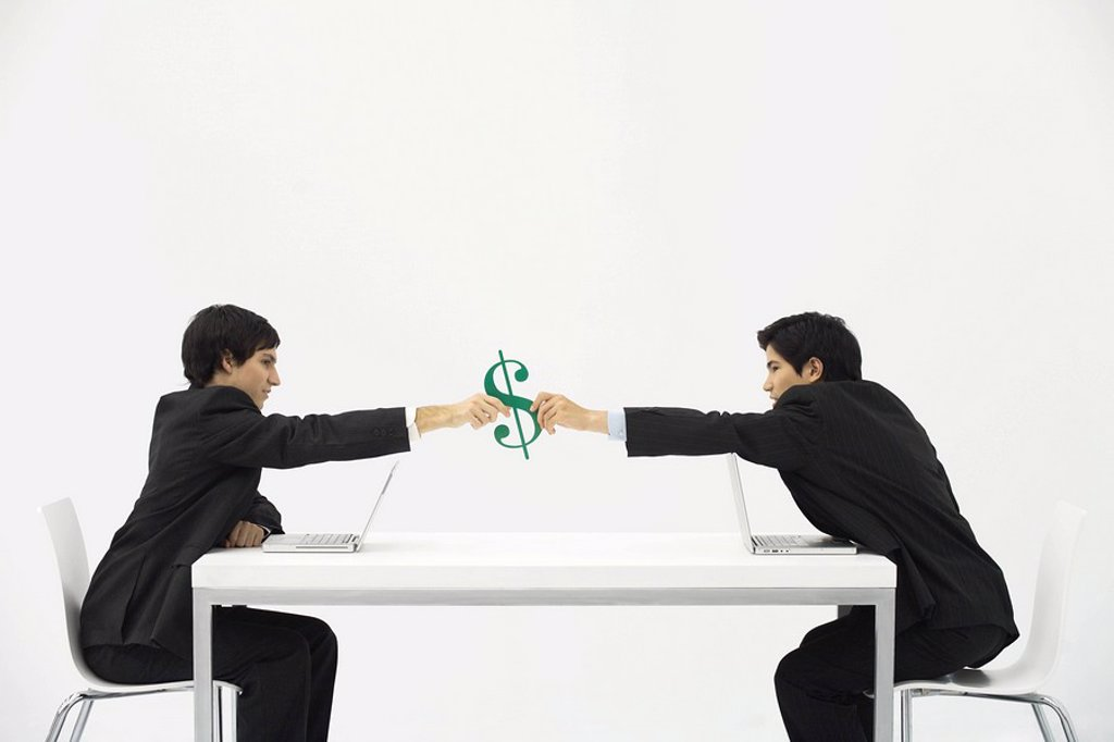 Businessmen sitting face to face at table, each reaching to hold dollar sign : Stock Photo