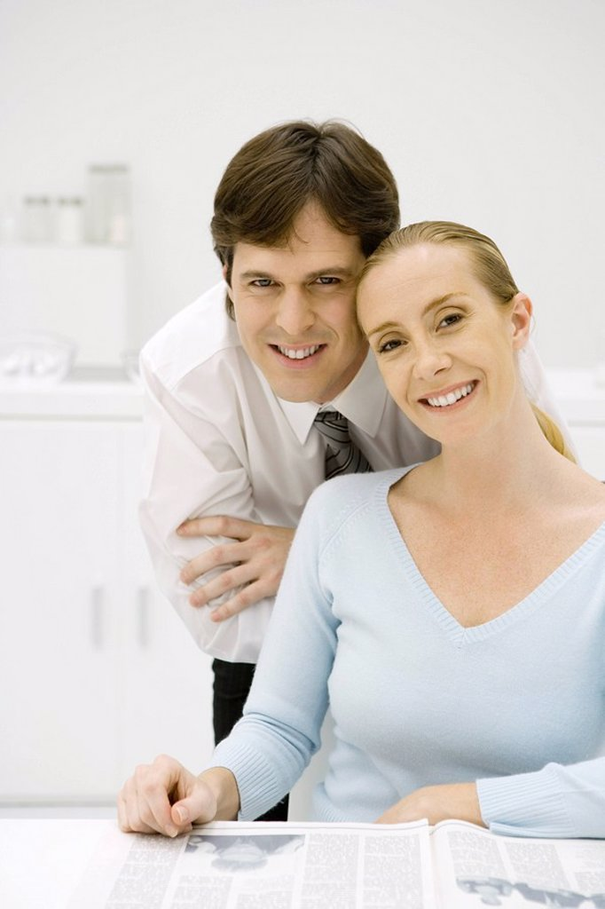 Stock Photo: 1569R-9036621 Couple smiling at camera together, woman sitting, man leaning over her shoulder