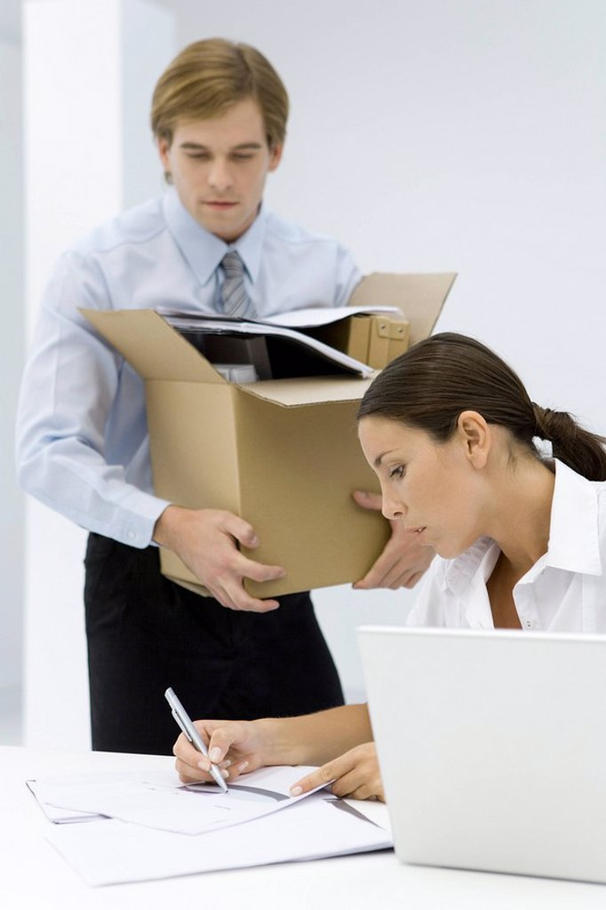 Woman writing on document at desk, man carrying cardboard box full of office supplies : Stock Photo