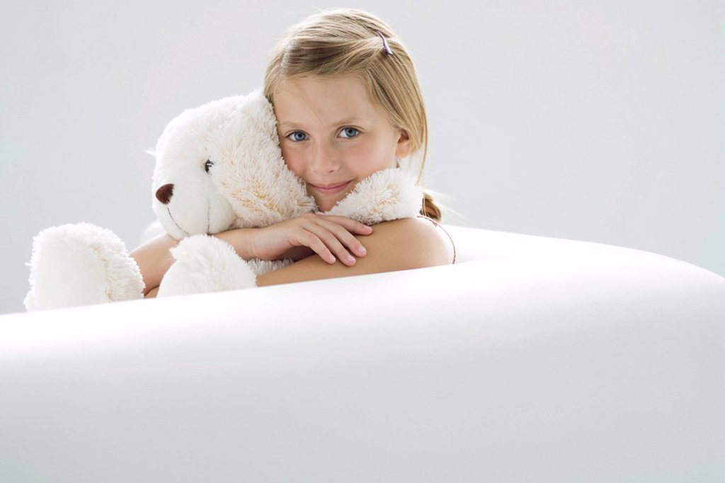 Stock Photo: 1569R-9036707 Girl holding teddy bear, smiling at camera