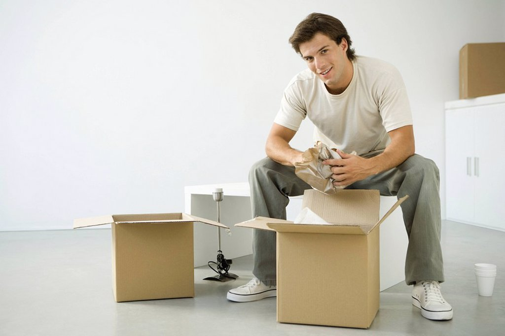 Stock Photo: 1569R-9036806 Man unpacking boxes, sitting on bench, smiling at camera