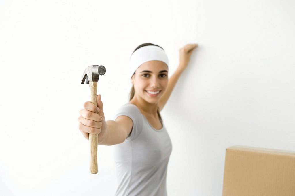 Stock Photo: 1569R-9036807 Teen girl showing hammer to the camera, smiling