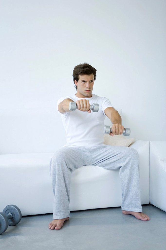 Young man sitting on sofa, lifting dumbbells : Stock Photo