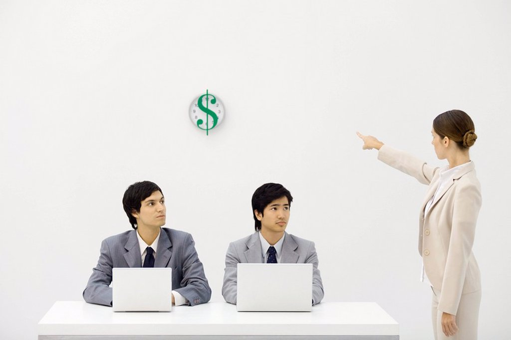 Two male office workers sitting at desk, female supervisor pointing at clock with dollar sign : Stock Photo