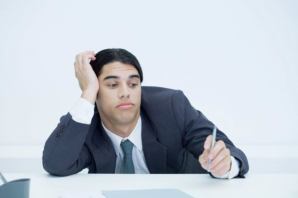 Stock Photo: 1569R-9037078 Young businessman slouching at desk, holding head and looking at pen with bored expression