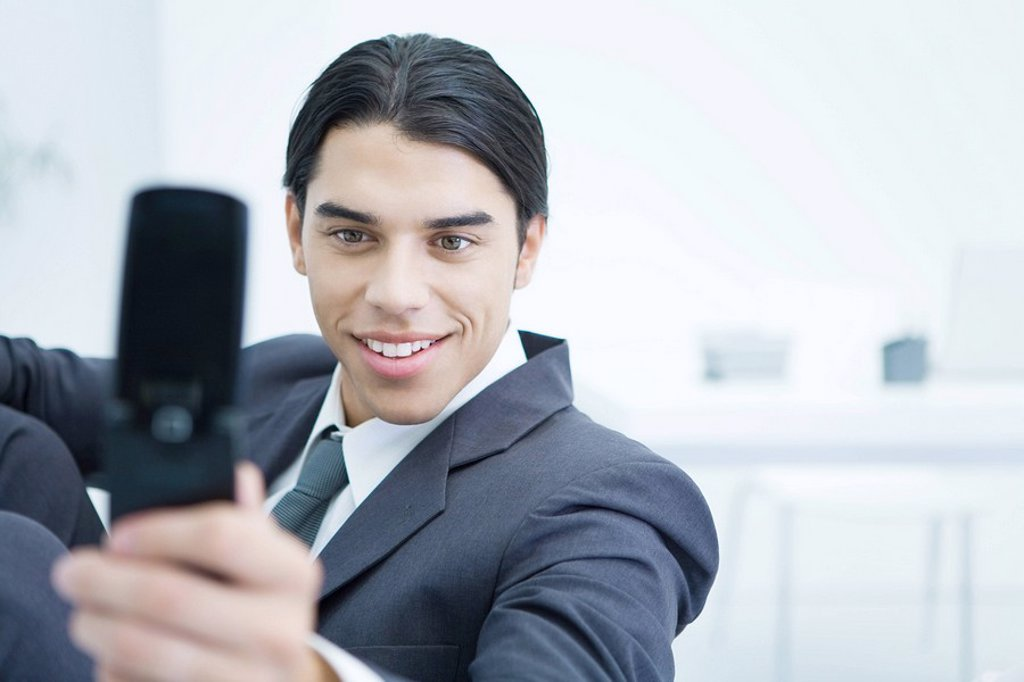 Stock Photo: 1569R-9037080 Young businessman using cell phone to take picture of himself, smiling