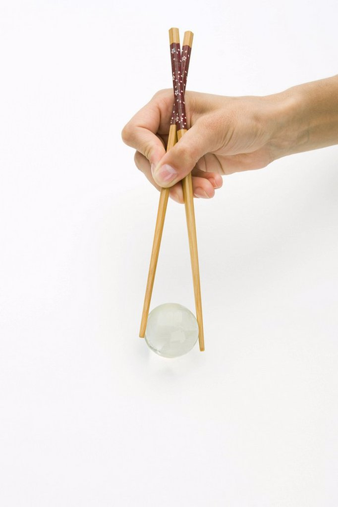 Stock Photo: 1569R-9037119 Hands using chopsticks to hold transparent globe, cropped view