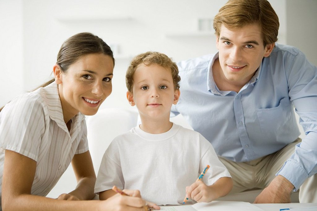 Little boy sitting with parents, drawing with pencil, all smiling at camera : Stock Photo