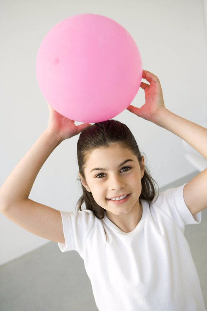 Girl holding balloon above her head, smiling at camera : Stock Photo