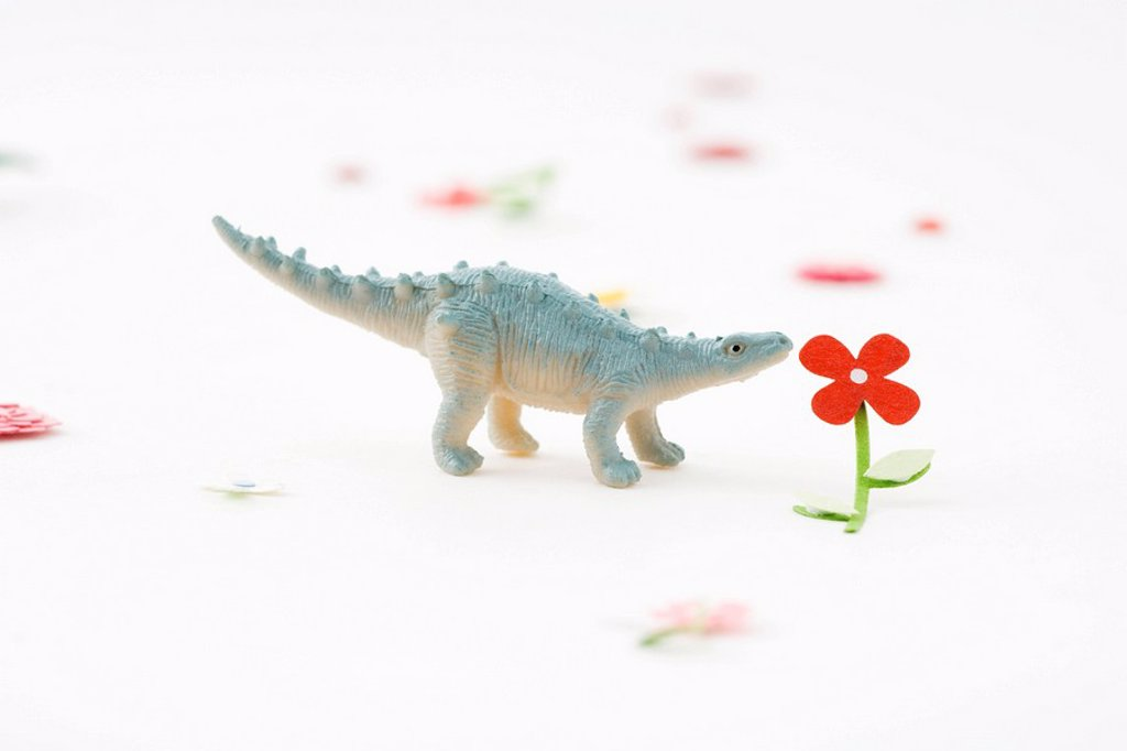 Toy dinosaur smelling artificial flower : Stock Photo