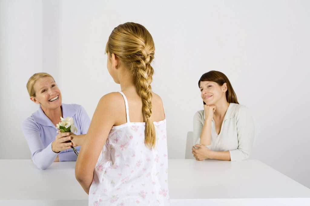 Preteen girl giving flower to her mother, another woman sitting nearby and smiling : Stock Photo