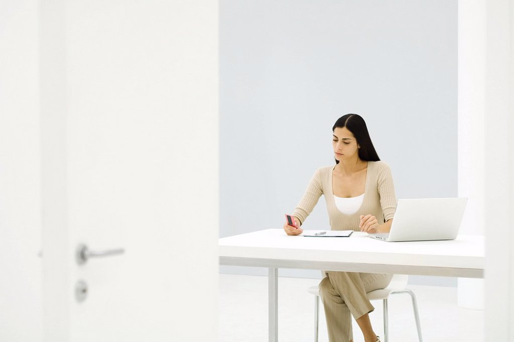 Stock Photo: 1569R-9037328 Businesswoman working alone in empty office