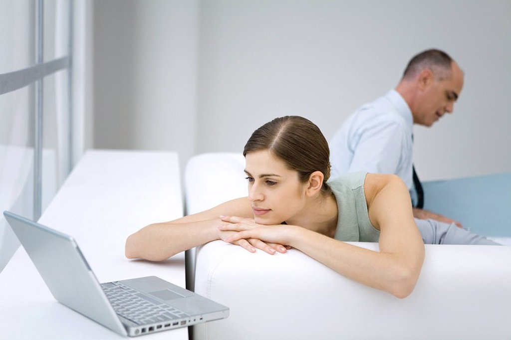 Young woman relaxing on sofa, using laptop computer, businessman reading in background : Stock Photo