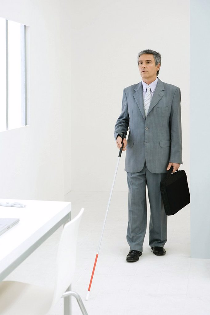 Blind businessman entering office, using white cane : Stock Photo