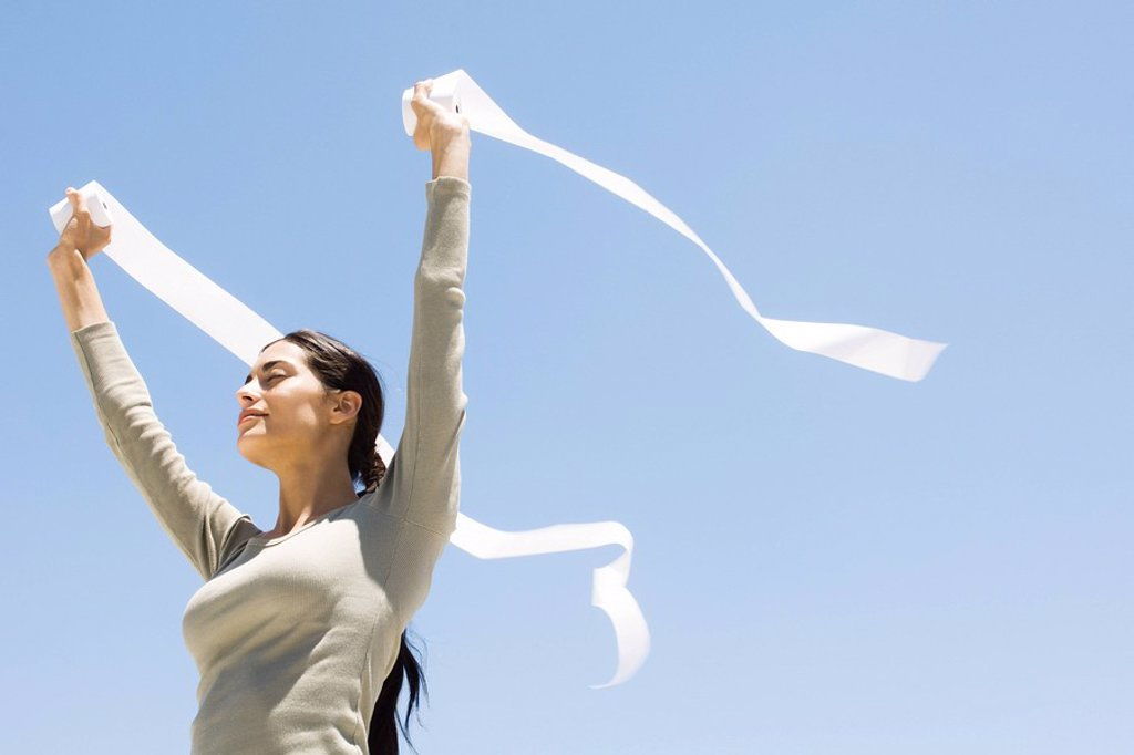 Woman holding up rolls of paper outdoors, eyes closed, low angle view : Stock Photo
