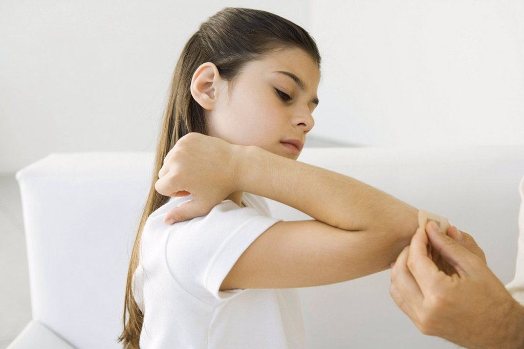 Man putting adhesive bandage on girl´s elbow, cropped view : Stock Photo