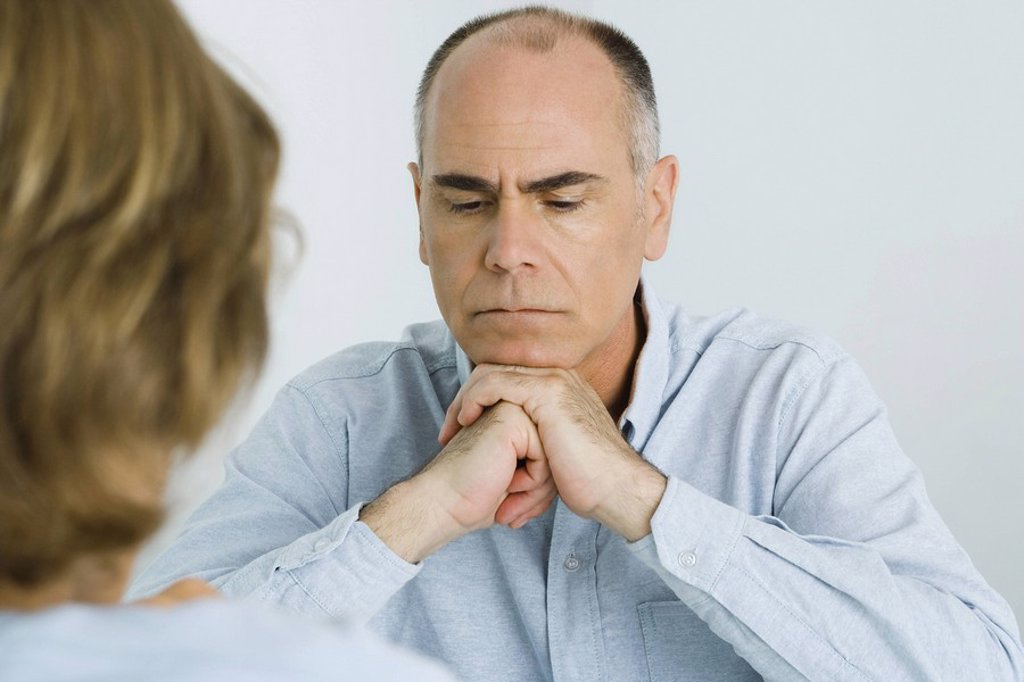Stock Photo: 1569R-9037621 Man resting chin on clasped hands, looking down, over the shoulder view