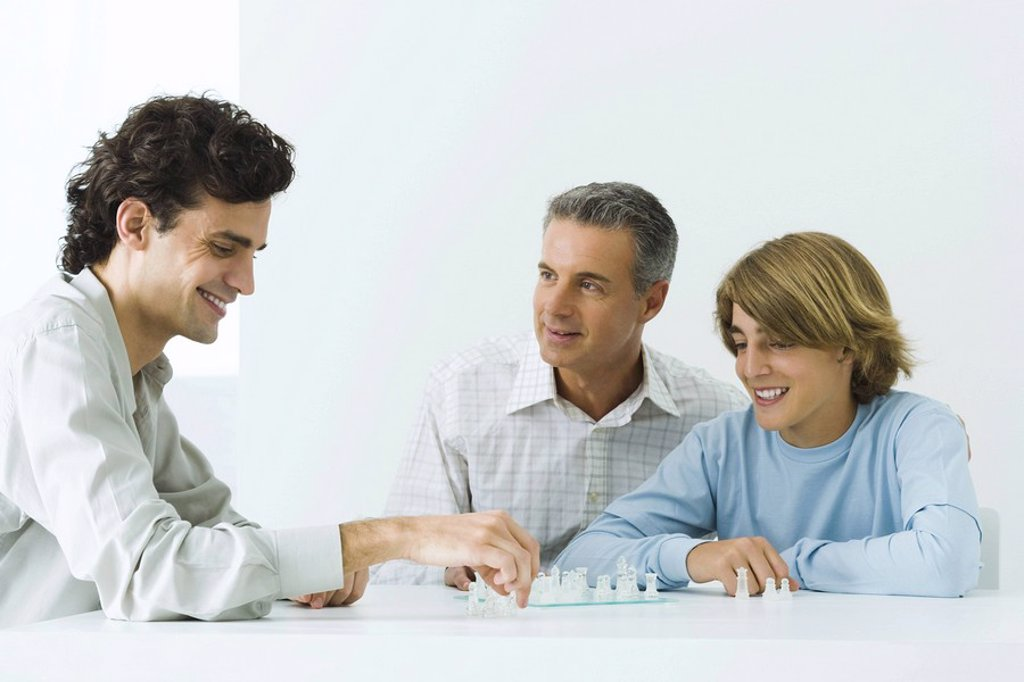 Stock Photo: 1569R-9037622 Mature father and two sons playing chess, all smiling