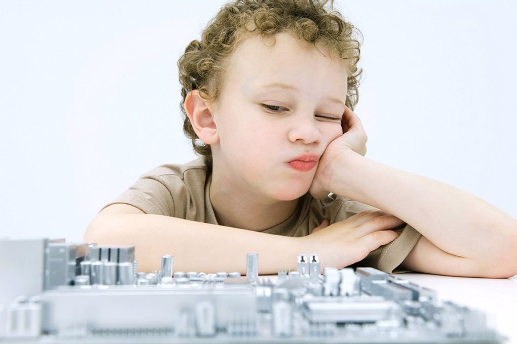 Little boy leaning on elbow, contemplating computer motherboard : Stock Photo
