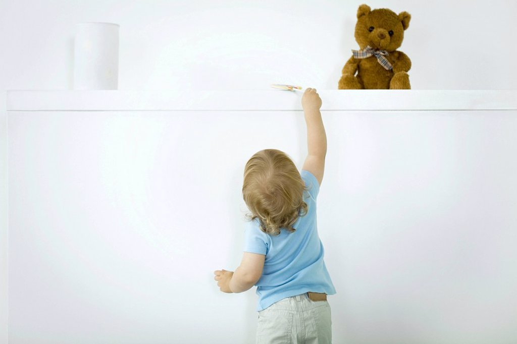 Stock Photo: 1569R-9037760 Toddler reaching for lollipop on high shelf, rear view