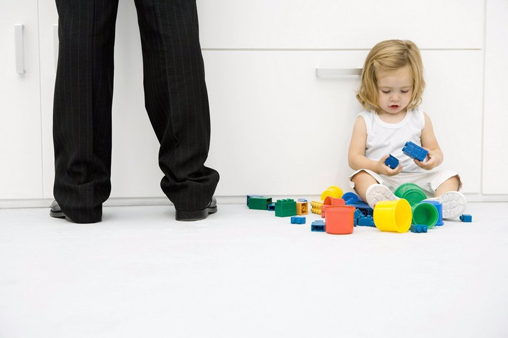 Toddler girl sitting on the ground beside father´s legs, playing with toys : Stock Photo