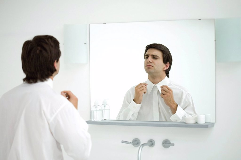 Stock Photo: 1569R-9037853 Man wearing button down shirt, adjusting collar in mirror