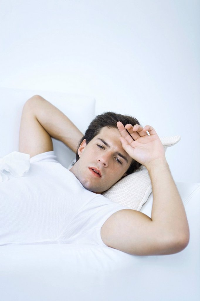 Stock Photo: 1569R-9037900 Man lying on sofa with tissue on his chest, hand on forehead