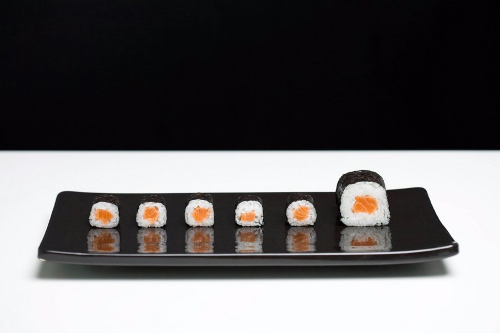 Maki sushi arranged on plate, one piece larger than the rest : Stock Photo