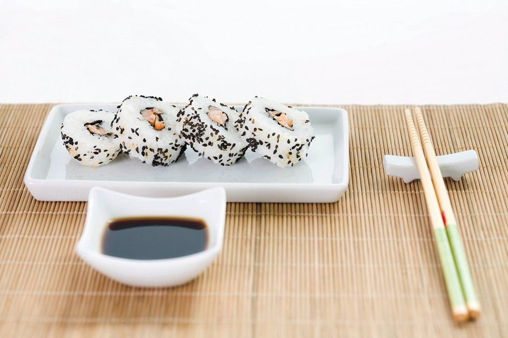 Maki sushi with soy sauce and chopsticks arranged on bamboo placemat : Stock Photo