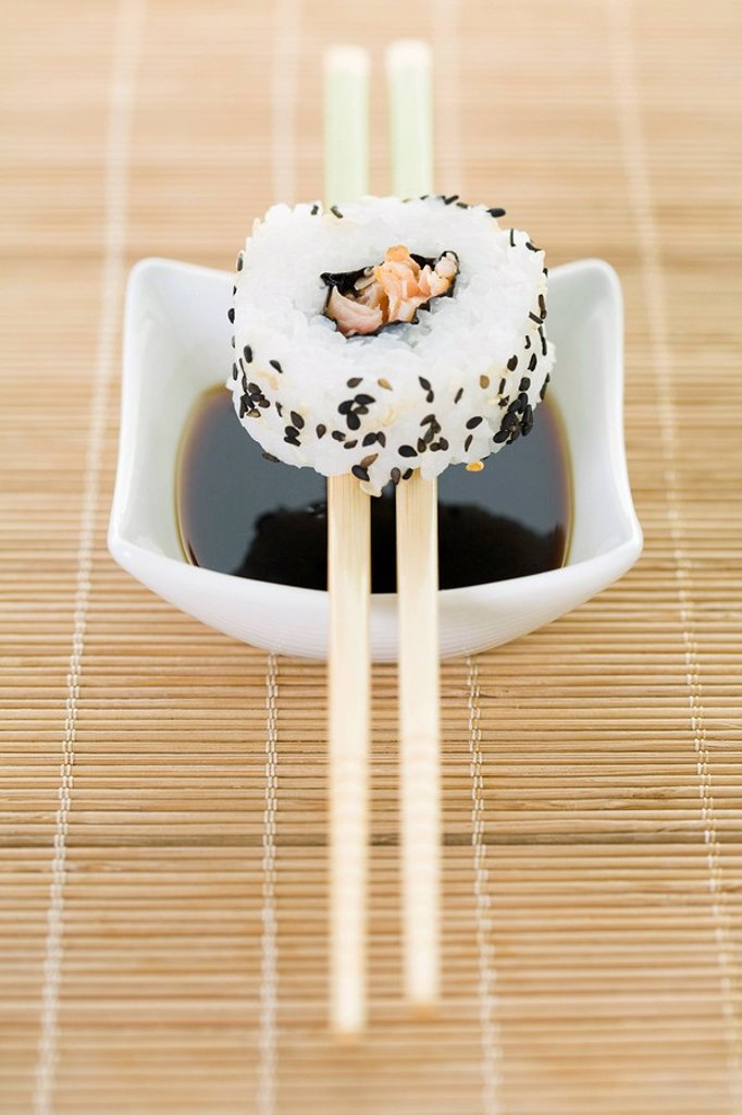 Stock Photo: 1569R-9037947 Maki sushi balanced on chopsticks over dish of soy sauce