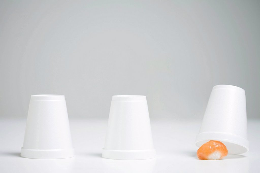 Stock Photo: 1569R-9037970 Three disposable cups in row, end cup lifted revealing single piece of nigiri sushi