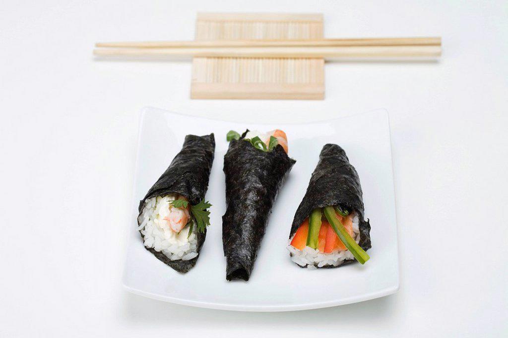 Stock Photo: 1569R-9037979 Temaki sushi on sushi plate with chopsticks
