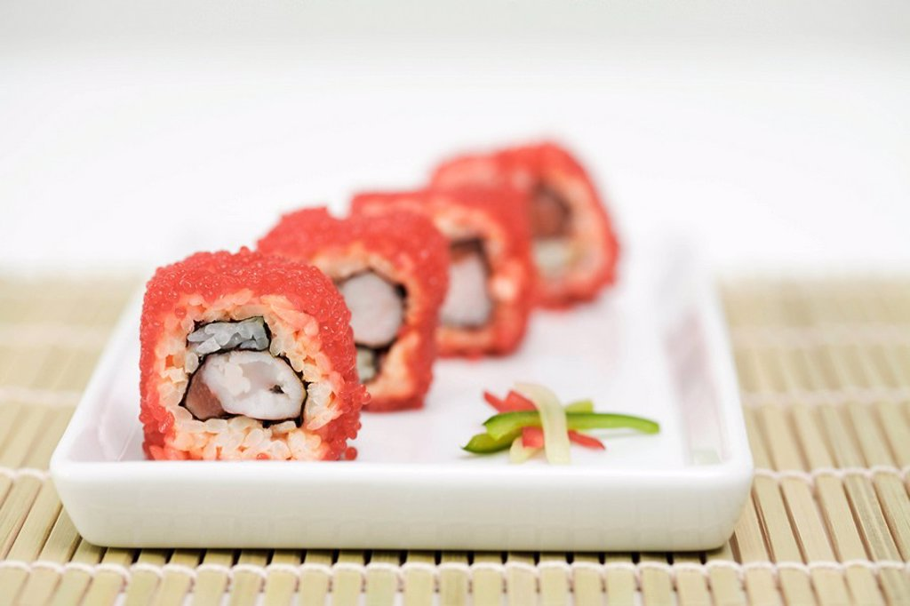Stock Photo: 1569R-9037991 Maki sushi rolled in red flying fish roe, cross section view