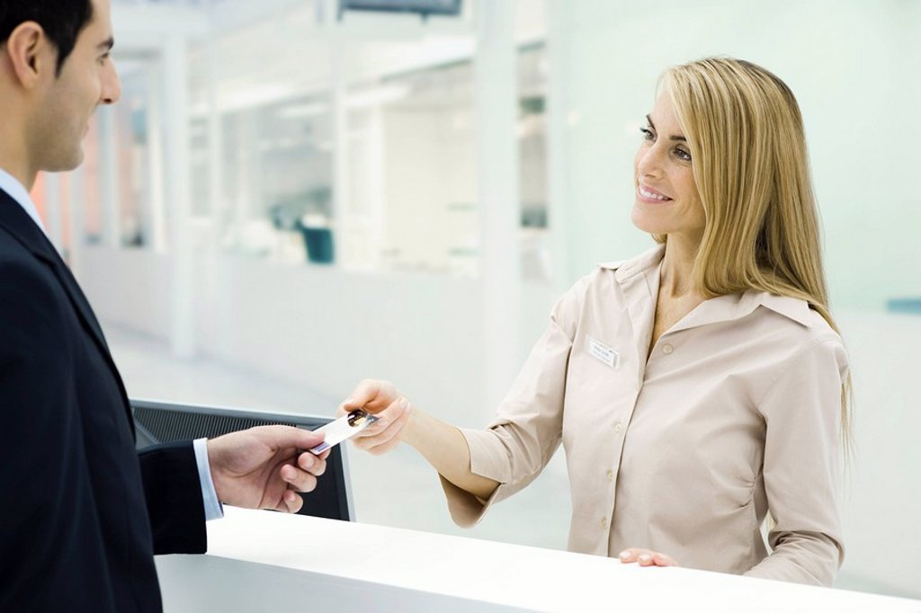 Stock Photo: 1569R-9038087 Customer handing credit card to customer service representative