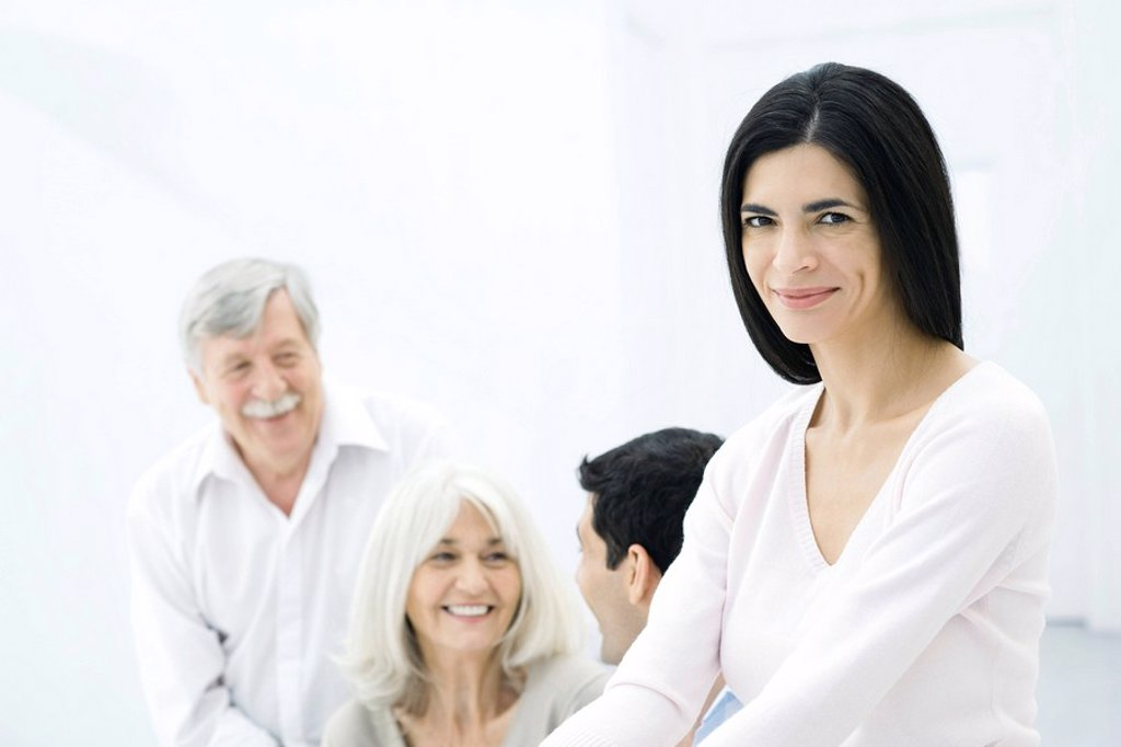 Woman smiling at camera, husband and parents in background : Stock Photo