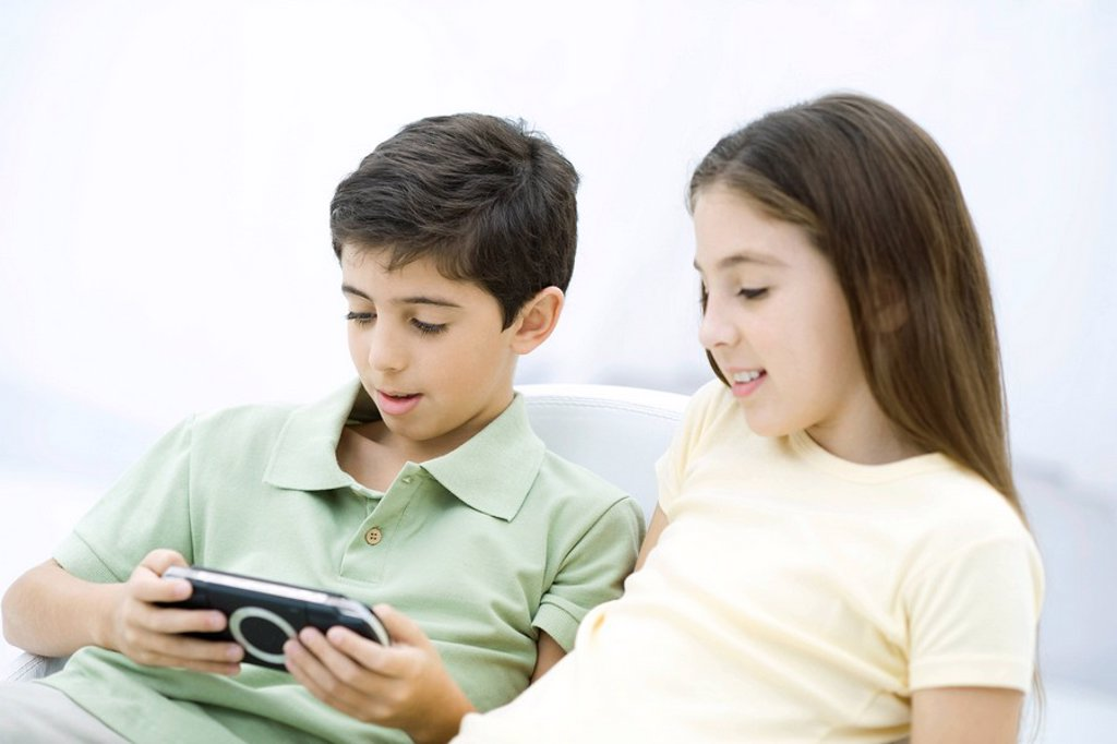 Brother and sister sitting together, boy playing handheld video game : Stock Photo
