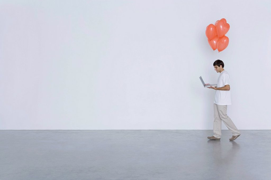 Stock Photo: 1569R-9038289 Man carrying laptop computer and heart balloons, side view
