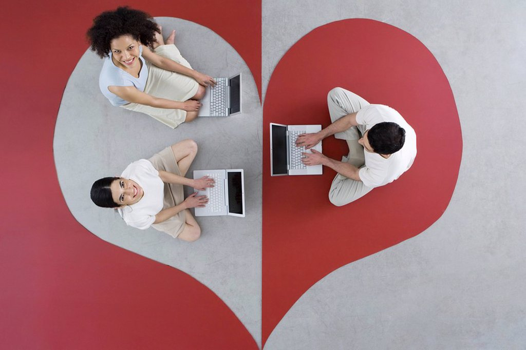 Two women and one man sitting on large heart, using laptop computers, women smiling up at camera : Stock Photo