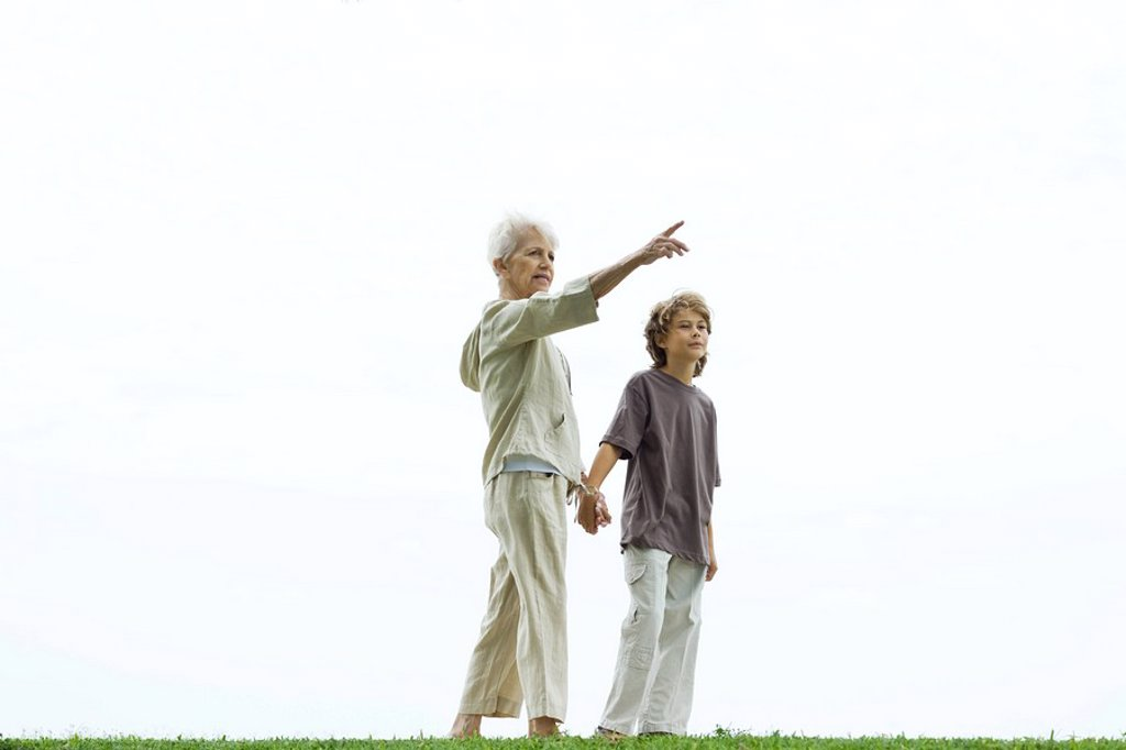 Grandmother walking hand in hand with grandson, pointing to the distance : Stock Photo