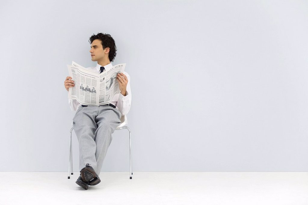 Stock Photo: 1569R-9038633 Businessman sitting in chair, holding newspaper, looking away