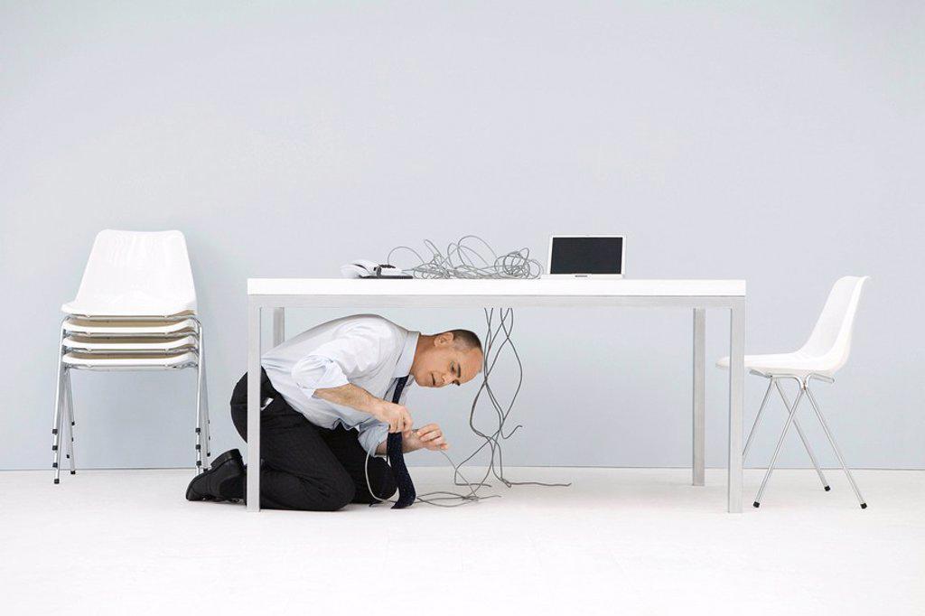 Businessman kneeling under table, examining cords : Stock Photo