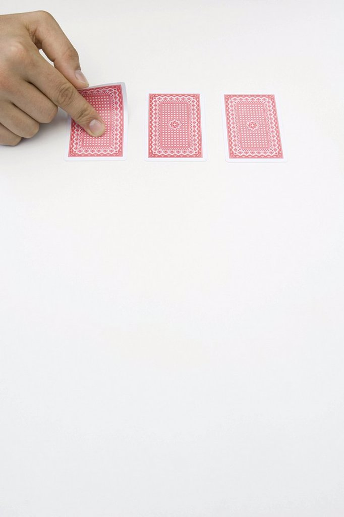 Stock Photo: 1569R-9038798 Hand turning over one of three cards