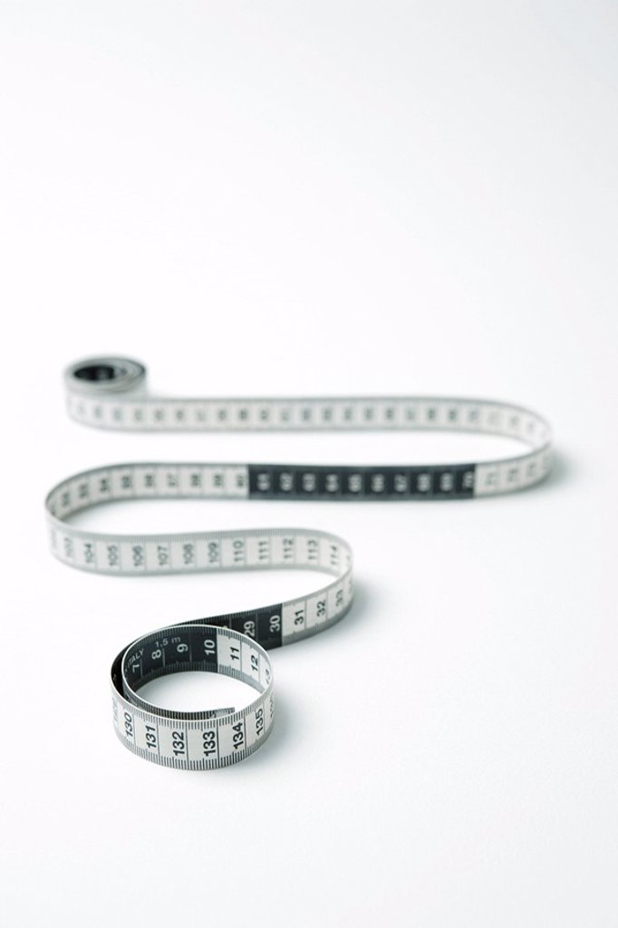 Stock Photo: 1569R-9039166 Measuring tape coiled in snakelike manor
