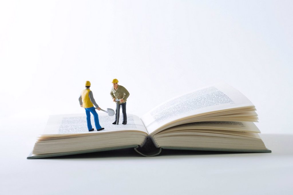 Miniature construction workers standing on open book : Stock Photo