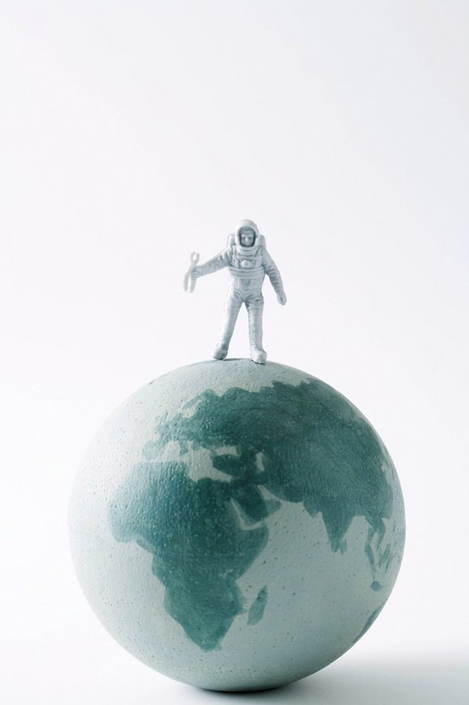 Stock Photo: 1569R-9039375 Miniature astronaut standing on top of globe