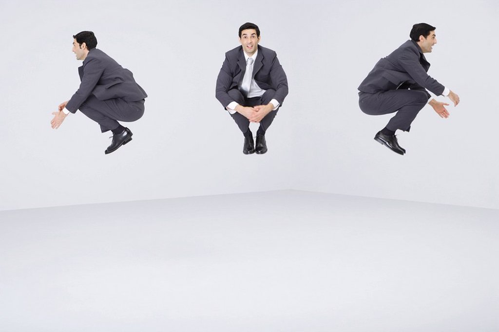 Identical businessmen jumping in midair : Stock Photo